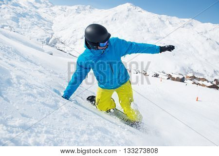 Snowboarder riding down the slope in the Alps