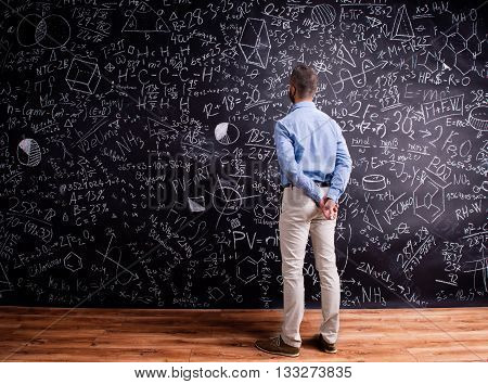 Hipster teacher standing against big blackboard with mathematical symbols and formulas, hands behind back. Studio shot on black background. Rear view.