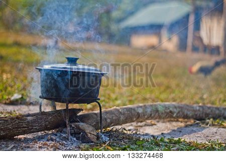 Dinner cooks in a large pot over an open fire