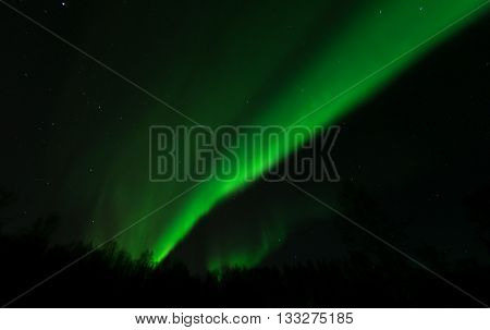 The wavefront of a green aurora pushes across the sky