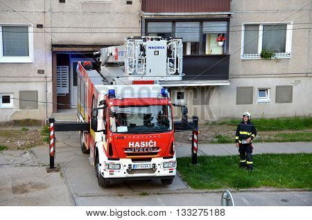 Bytca, Slovakia - June 4, 2016: Firefighter stand near the fire truck in action block of flats in background