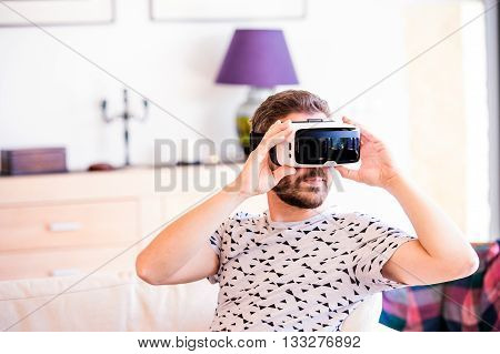 Young hipster man wearing virtual reality goggles, sitting in living room