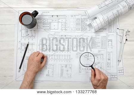 Close-up hands of architect while working process with magnifying glass. Top view composition. Workplace of architect or constructor. Non-stop work. Research and investigation. Deep scan. Engineering work. Construction and architecture. Architect drawing.