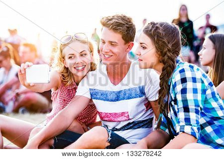 Group of teenage boys and girls at summer music festival, sitting on the ground, taking selfie with smart phone
