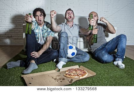 group of friends fanatic football fans watching soccer game on television celebrating goal on grass carpet emulating stadium pitch screaming excited and ecstatic crazy happy with beer and pizza