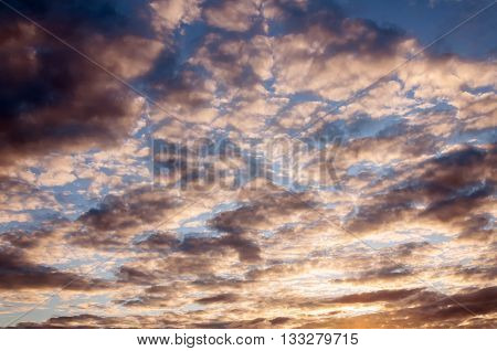 Cumulus sunset clouds with sun setting down. Summer evening sky and clouds