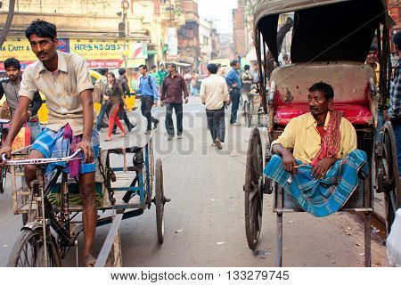 KOLKATA, INDIA - JAN 21, 2013: The hand-pulled rickshaw and cycle rickshaw met on the crowd street on January 21, 2013. Kolkata's Rroad Space was only 6 perc. compared to 23 perc. in Delhi