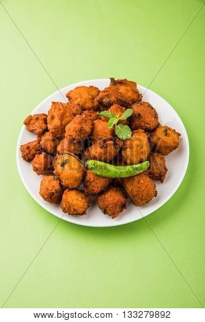 Delicious Tasty and Yummy Indian Moong Dal vada or moong dal pakoda or moong vada or moong vade or Pakora (Fritter) with fried green chilli, red and green hot sauce.
