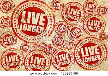 live longer, red stamp on a grunge paper texture