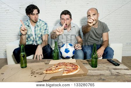 group of friends fanatic football fans watching soccer game on television with beer bottles and pizza suffering stress and crazy nervous on couch complaining gesturing no with finger
