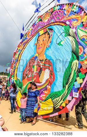 Sumpango Guatemala - November 1 2015: Visitors pose for photos in front of handmade kite with indigenous theme at giant kite festival honoring spirits of dead on All Saints' Day.