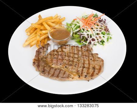 Rib eye steak served with french fries and salads to vegetables isolated on the black background with clipping path