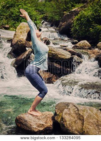 Vintage retro effect hipster style image of sporty fit woman doing yoga asana Utkatasana (chair pose) outdoors at tropical waterfall standing on stone