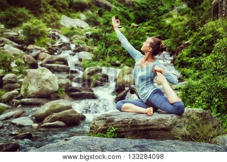 Vintage retro effect hipster style image of sporty fit woman doing yoga asana Eka pada rajakapotasana - one-legged king pigeon pose at tropical waterfall