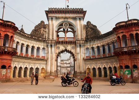 AYODHYA, INDIA - JAN 27, 2013: Motorbike riders move past the beautiful historical Raj Sadan gates on January 27, 2013 in Ayodhya. Ayodhya with a population of 49593 is birthplace of Lord Rama