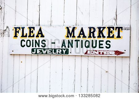 An old flea market sign on a white barn.