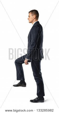 Side view of businessman climbing stairs , isolated on white background. Business staff. Office clothes. Dress code. Presentable appearance. Self-confidence.