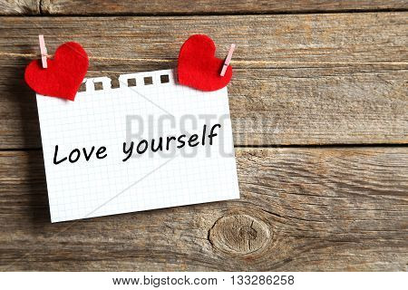 Blank paper hanging on rope on grey wooden background, love yourself