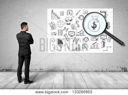 Back view of businessman looking at the bag of money through the magnifier. Economic and statistical graphs. Increase in profits. Making money. Prosperous business. Srategic calculation and research. Financial and business concept. Business idea.