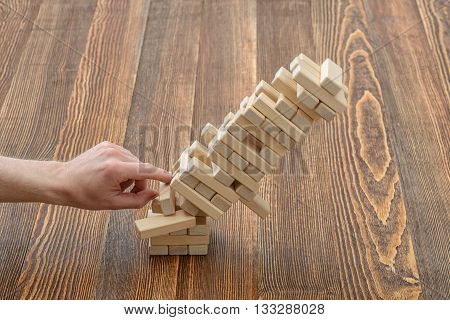Hands of man pushed the brick and destroyed the tower. Close-up photo. Imbalance. Collapse and destruction. Mistake. Entertainment activity. Game of physical and mental skill. Removing blocks from a tower.