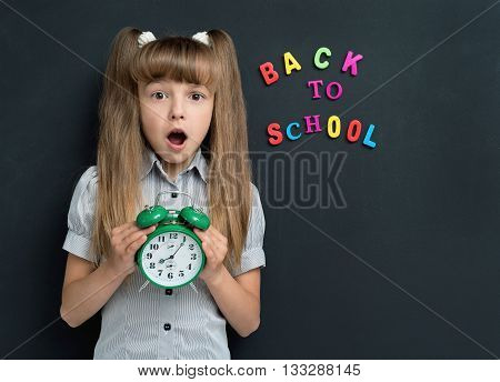 Back to school concept. Shocked schoolgirl with alarm clock at the chalkboard.
