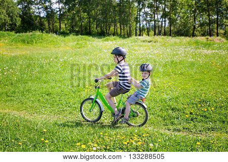 two young bicyclist on a bicycle. elder brother carries his younger brother on the bike on a blossoming meadow. copy space for your text