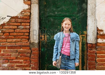 Outdoor portrait of fashion little girl of 7-8 years old, wearing denim skirt and jacket, standing against old facade. Young tourist in Italy
