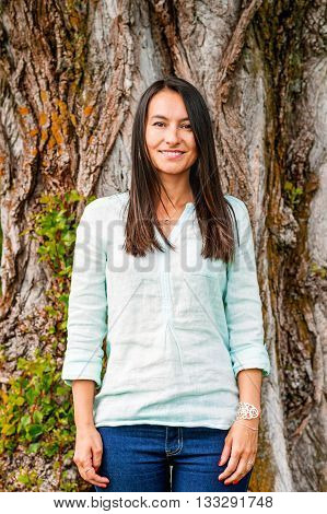 Stylish cheerful brunette leaning on a tree in a park on a sunny day, wearing denim jeans, mint blouse