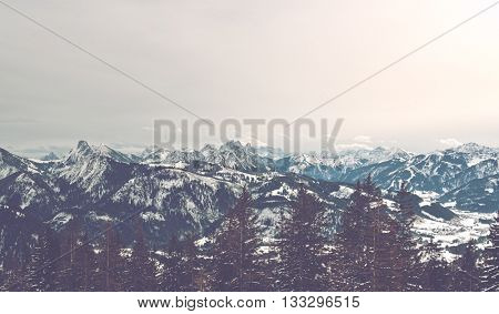 Wide view of Alps mountain range and line of forest in background of ski hill