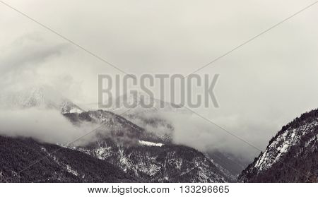 Dark winter clouds looming over snow covered mountains partially covered by snow