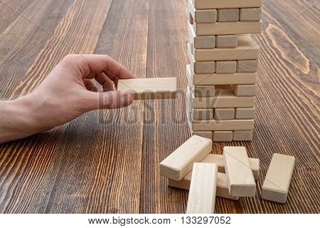 Close-up hands of man playing with wooden bricks. Entertainment activity. Education and development. Full concentration. Game of physical and mental skill. Removing blocks from a tower. Keeping balance.