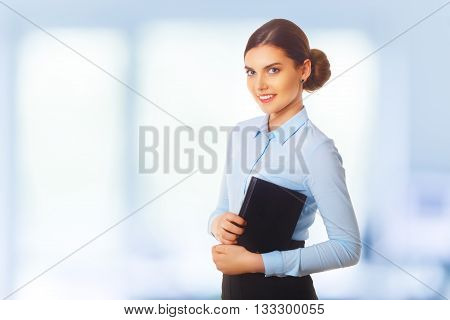 Portraitof happy smiling young cheerful businesswoman in blue clothing. Hold diary in her arms. Standing in her office. Blue background.