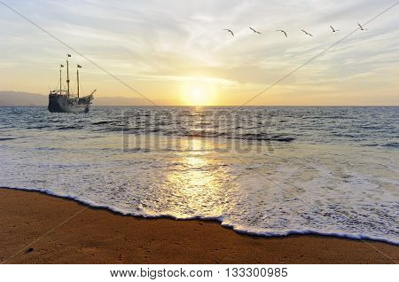 Pirate ship is a a pirate ship facing the sunset as a flock of gulls fly by.