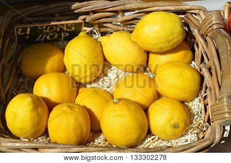 Several fresh yellow lemons in a basket