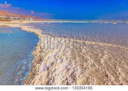 Vaporized salt form whimsical patterns on the water surface. Dead Sea off the coast of Israel