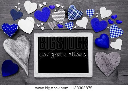 Chalkboard With English Text Congratulations. Many Blue Textile Hearts. Grey Wooden Background With Vintage, Rustic Or Retro Style. Black And White Style With Colored Hot Spots