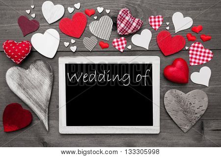 Chalkboard With English Text Wedding Of. Copy Space For The Names Of The Couple. Many Red Textile Hearts. Grey Wooden Background With Vintage Style. Black And White Style With Colored Hot Spots