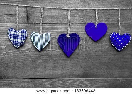 Wooden Background With Blue Hearts Hanging In A Row. Black And White Style With Colored Hot Spots. Copy Space For Advertisement Or Free Text. Greeting Card For Valentines Or Mothers Day