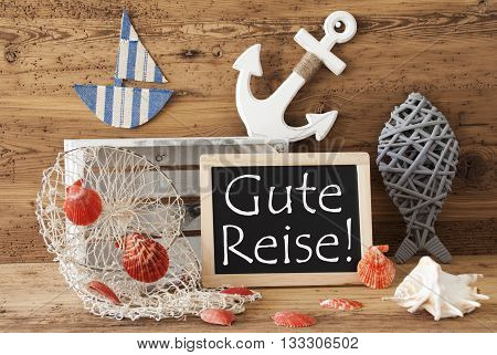 Blackboard With Nautical Summer Decoration And Wooden Background. German Text Gute Reise Means Good Trip. Fish, Anchor, Shells And Fishnet For Maritime Contex.