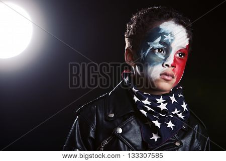 Adorable, mixed race boy, wearing red, white and blue face paint, a stars and stripes bandanna and a leather jacket.  Background light for effect.