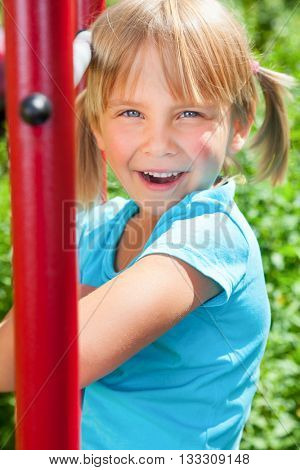 Portrait of cute blond girl with blue eyes wearing blue tshirt sitting on monkey bars on a summer day. Girl looking at camera smiling. The climbing frame is located in the courtyard of a house