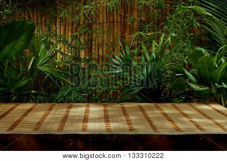 spa background. View of tropical green foliage with bamboo mat