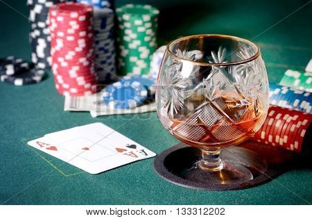 Poker table with glass of cognac or whiskey, casino chips and playing cards