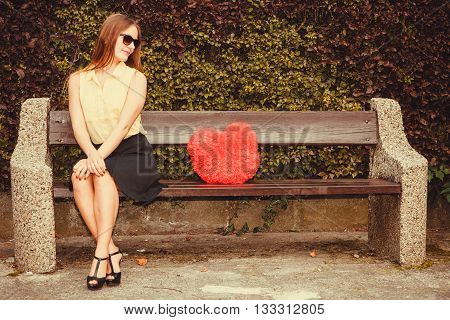Love romance loneliness concept. Smiling girl sitting on bench. Cheerful lady with heart symbol.