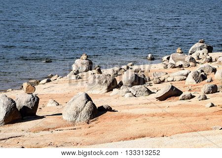 Rocky beach on the foreshore of Lake Jindabyne, featured in the background