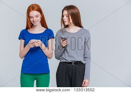 Two smiling depressed young women standing and using cell phones