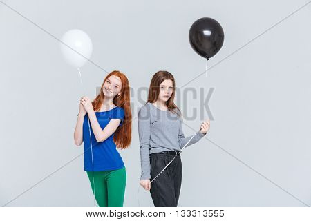 Two cheerful and upset young women holding black and white balloons