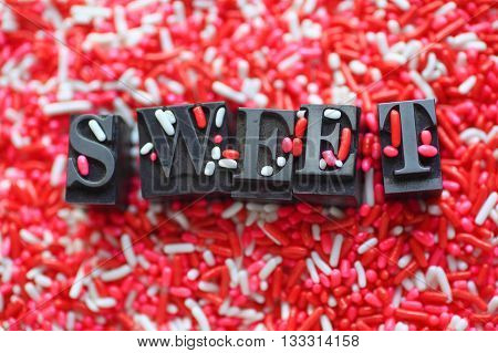 The word 'sweet' in metal type on a pink and white candy sprinkles background