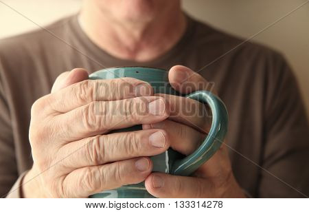 Older man warms his hands with a cup of hot coffee.