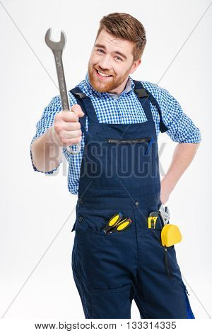 Smiling bearded young man standing and showing wrench
